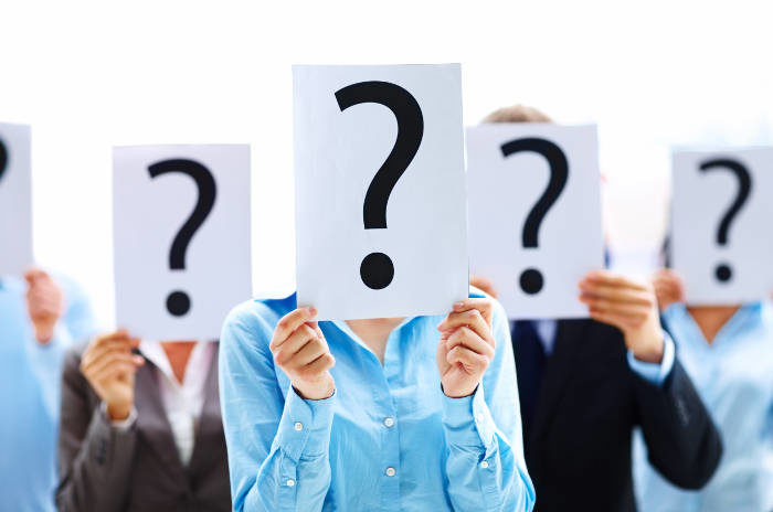 Risk management professionals holding question marks